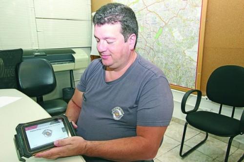 Major Ricardo mostra o tablet que os policiais utilizam nas viaturas